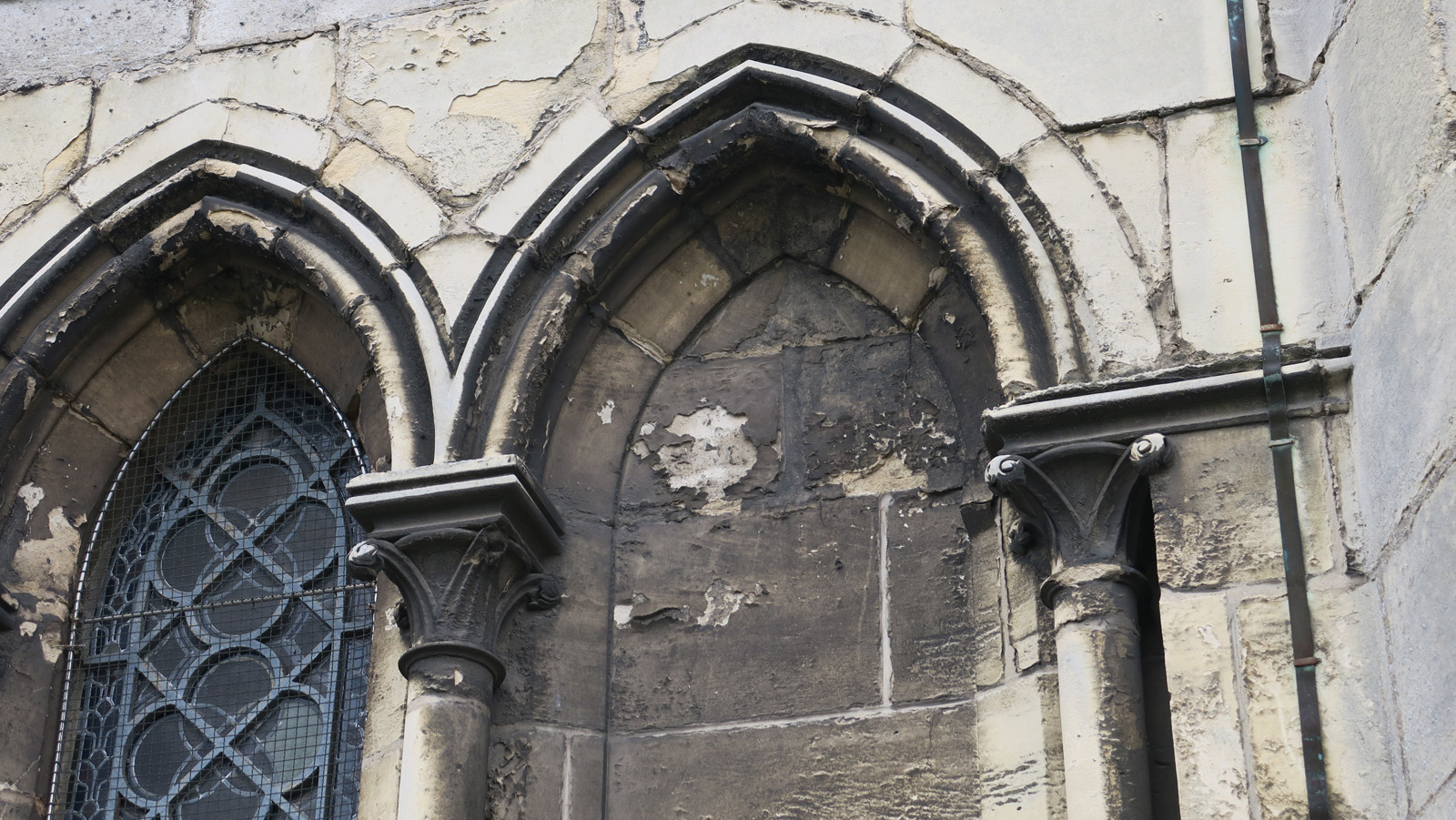 Desquamation de la pierre de l'ogive sous l'action de l'eau et de la pollution – extérieur de la sacristie
