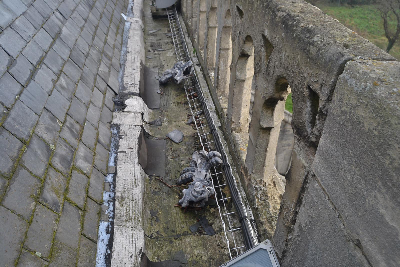 Vue des éléments décoratifs de faitage tombés dans le chéneau de toiture (2014)